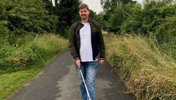 Mark walking in the countryside with a cane