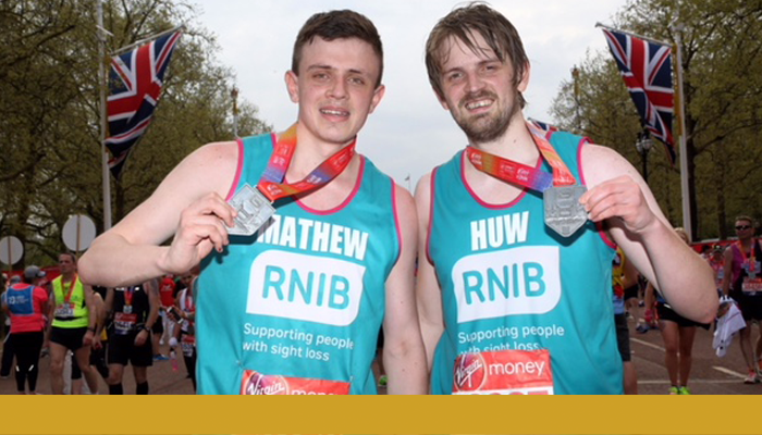 Matthew Rowcliffe and his brother Huw wearing RNIB running t-shirts and holding a Virgin London Marathon 2018 medal around their necks. A gold bar spans below the photo.