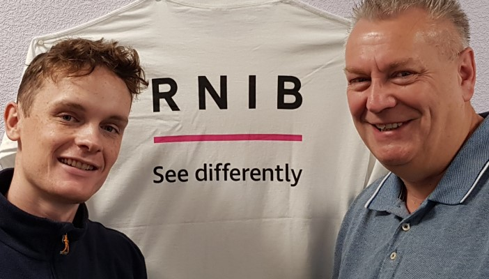 Lewis and Mike pose infrom of a white t-shirt with the RNIB logo on it