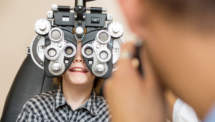 Preadolescent boy smiling while undergoing eye test with phoropter