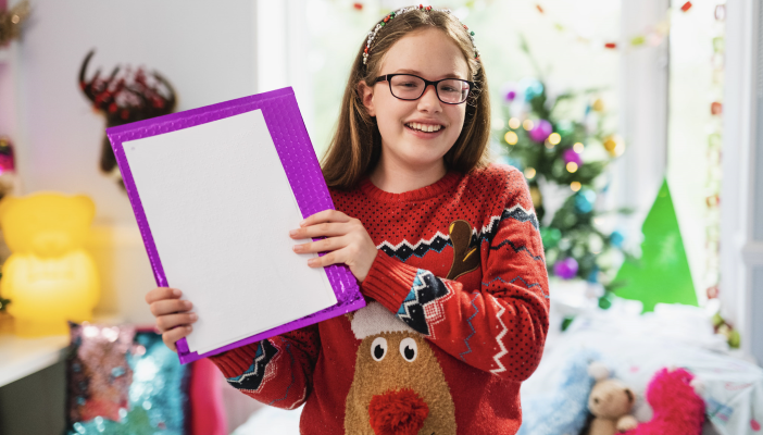 Keira smiles holding a braille letter from Santa