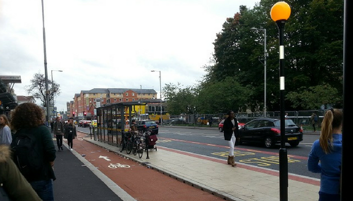 Pedestrians walk on the pavement around a bus stop bypass on Oxford Road, Manchester
