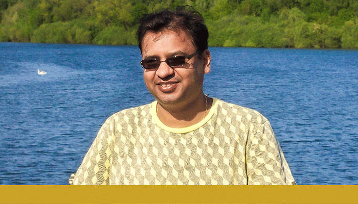 Paresh smiling at camera and wearing sunglasses in front of a lake. A gold bar spans below the photo.