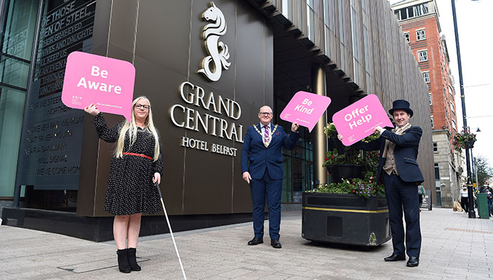 People holding signs highlighting social distancing outside the Grand Central Hotel, Belfast
