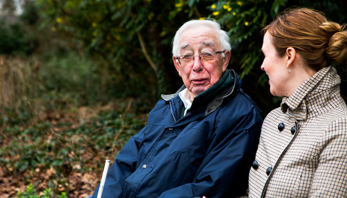 A man of advanced age holding a cane sitting next to a woman outdoors