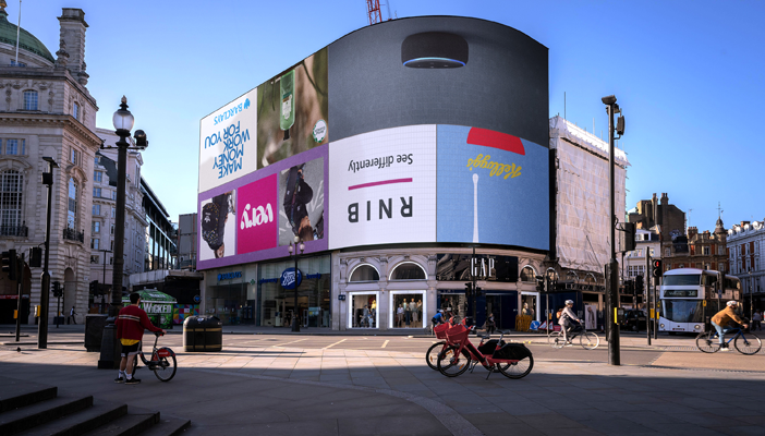Image shows the Piccadilly Lights billboard with various adverts, including the RNIB logo, turned upside down.