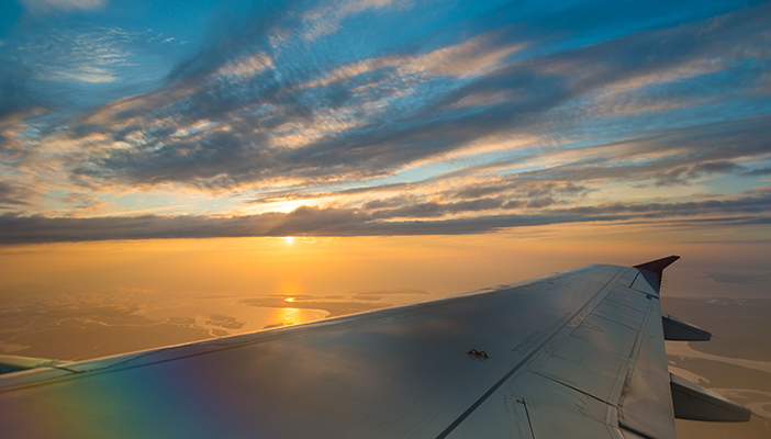 Image shows the view from a plane, including the planes wing and a sunset in the distance