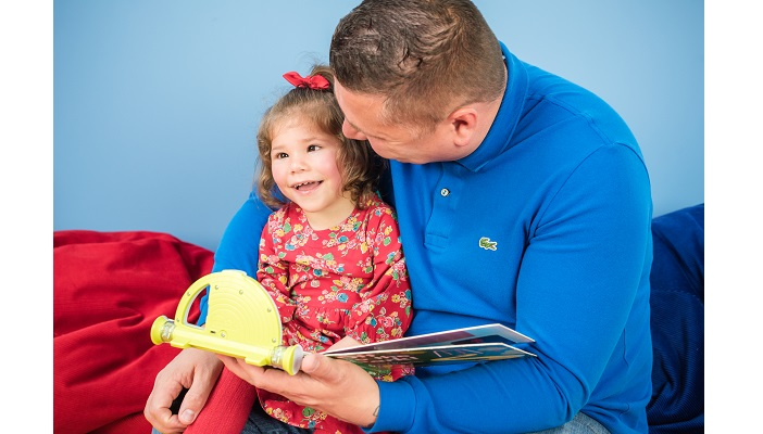 Image of Dad and daughter playing with a talking book together