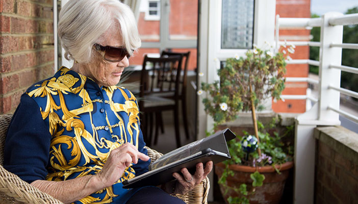 Older woman with short grey hair and dark glasses sitting on her balcony using a tablet