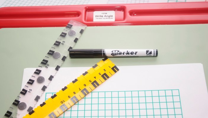 Photo of a Write Angle writing slope, black market pen, thick-lined grid paper and tactile rulers