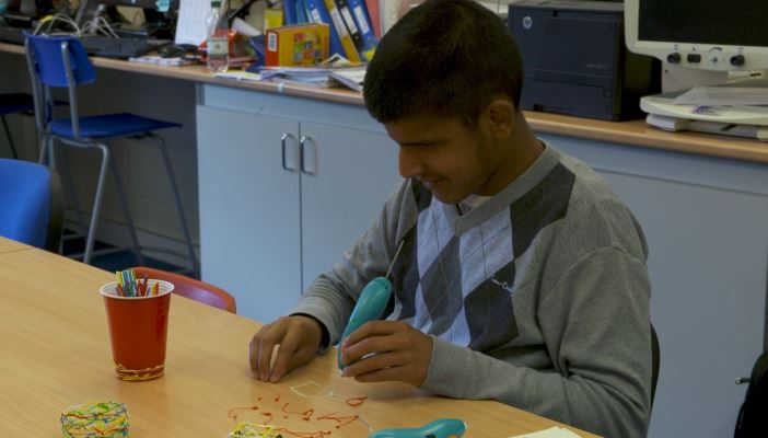 Photo of boy creating with a 3Doodler pen at school