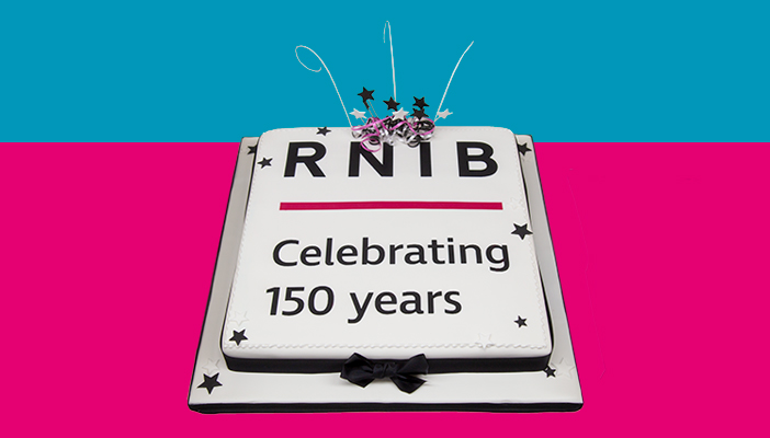 Cake with white icing with writing in black icing that says RNIB Celebrating 150 years