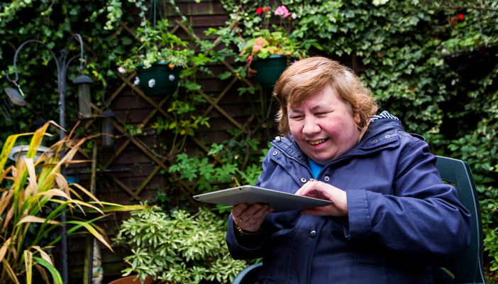 A woman using an iPad outdoors with a smile on her face