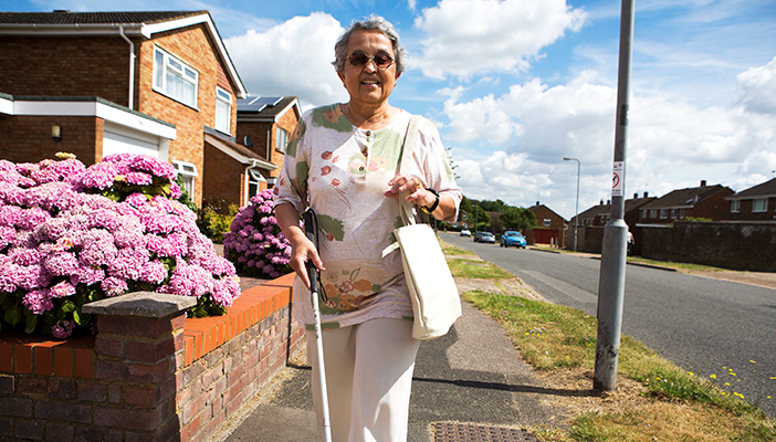 Lady walking with cane in hand