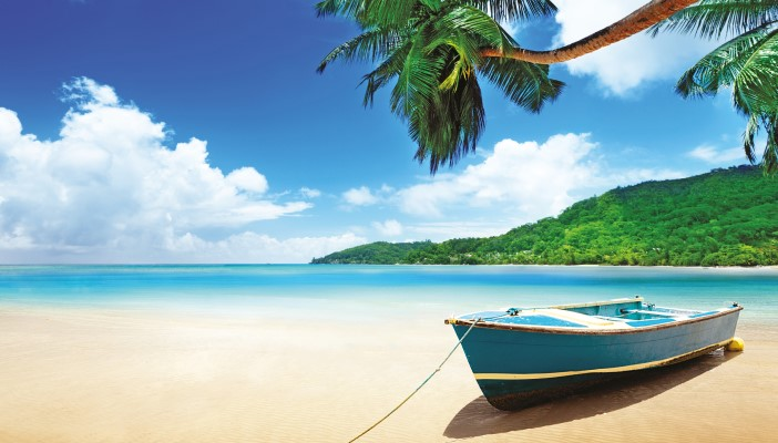 Row boat on tropical beach next to a calm azure sea