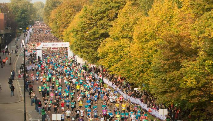 Image shows a view of hundreds of people running a marathon with lots of greenery and trees on the sidelines