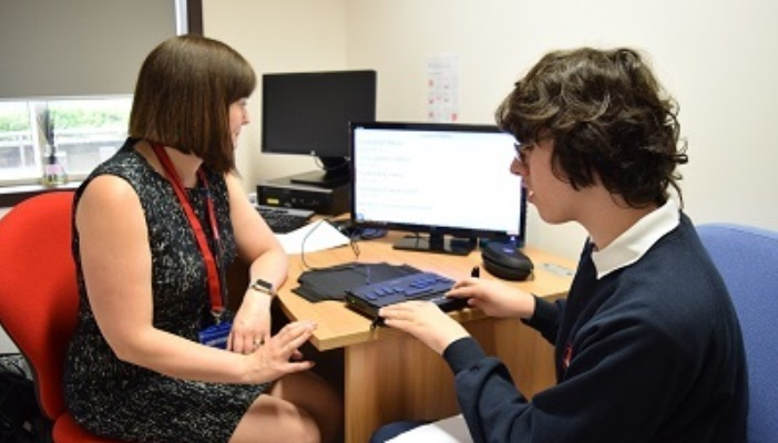 Photo of a young person with vision impairment using a braille keyboard in a room with a professional