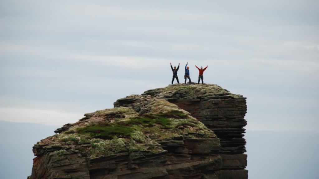 Red Szell and his friends stand on a rocky outcrop