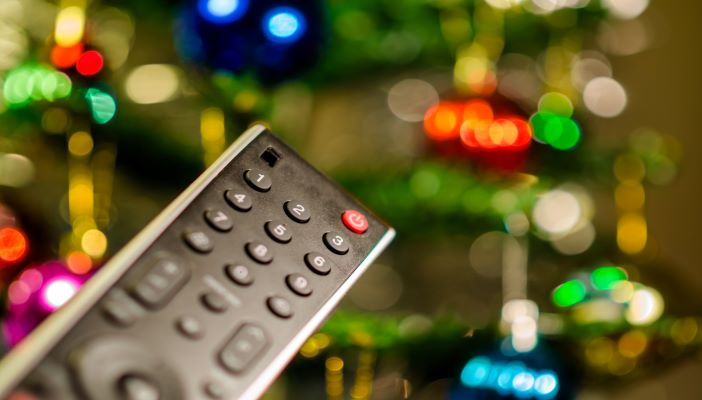 A TV remote with Christmas lights in the background