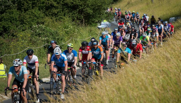 Image shows a line of many people on bicycles in the countryside during the Ride London event