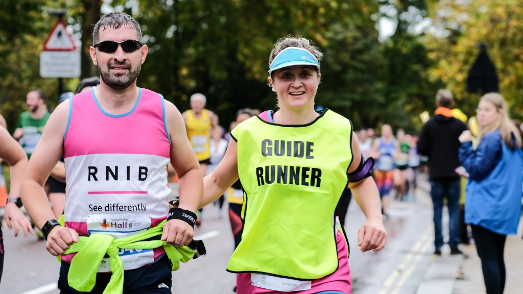 Member of Team RNIB and their guide runner at a running event.