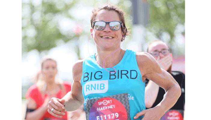 Image shows a woman running during the race, wearing sunglasses and an RNIB t-shirt with a smile on her face