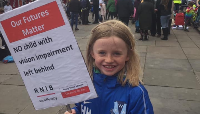 Image shows young child holding a placard that contains the RNIB and Young Vision Alliance logos and reads 'Our future matters, no child with vision impairment left behind'.