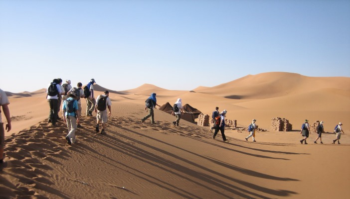 Image shows a group of people trekking through the desert