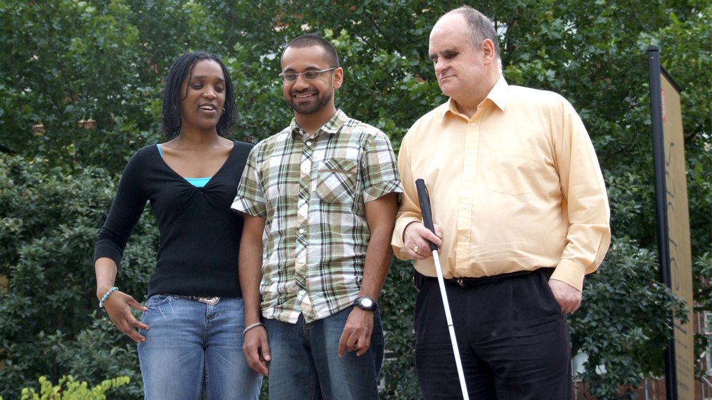 Three blind or partially sighted people standing together outside