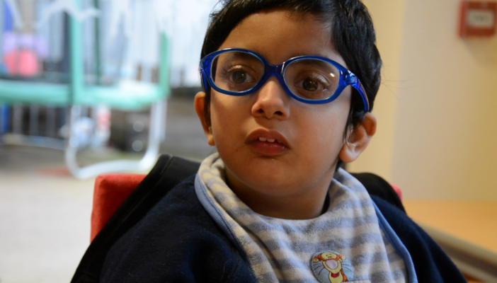 Child with vision impairment wearing glasses