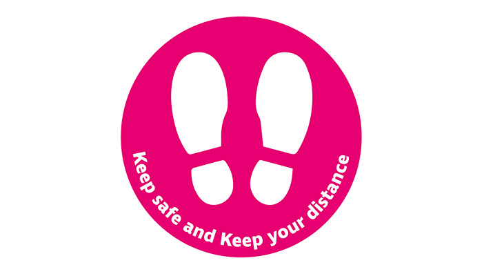 A pink circle with two white footprints, under which it reads 'Keep safe and keep your distance'