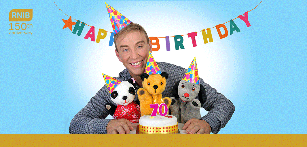 Richard stood behind Sooty, Sweep and Su smiling with a cake in front of them with candles on it in the shape of the number seventy