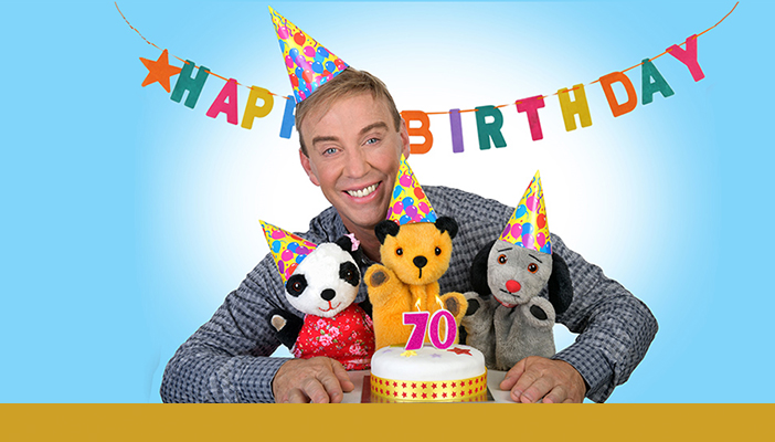Richard stood behind Sooty, Sweep and Su smiling with a cake in front of them with candles on it in the shape of the number seventy. A gold bar spans across the bottom of the photo.