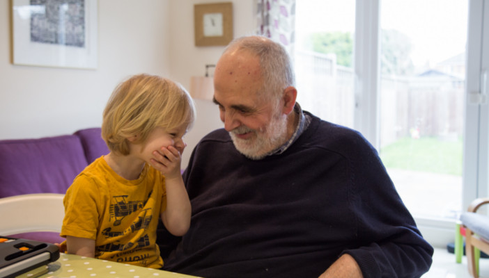 A Grandfather and Grandson share a joke reading a story