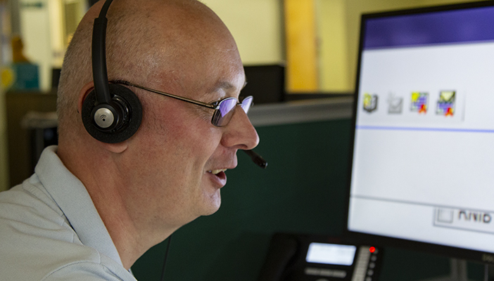 Helpline adviser with headset in front of a computer screen