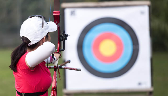 Woman aiming a bow and arrow at target