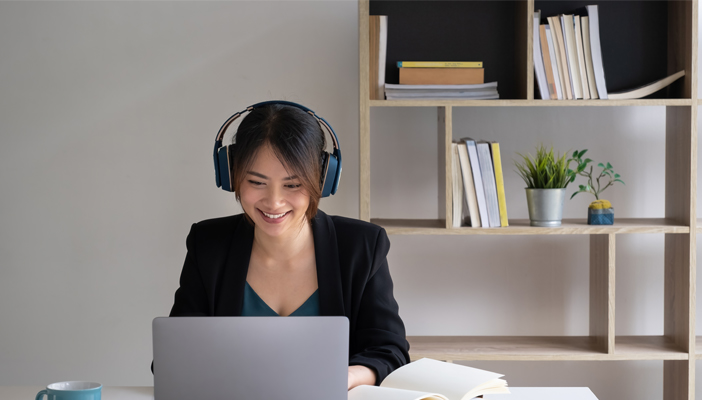 Woman in headphones sits at a desk before a computer.