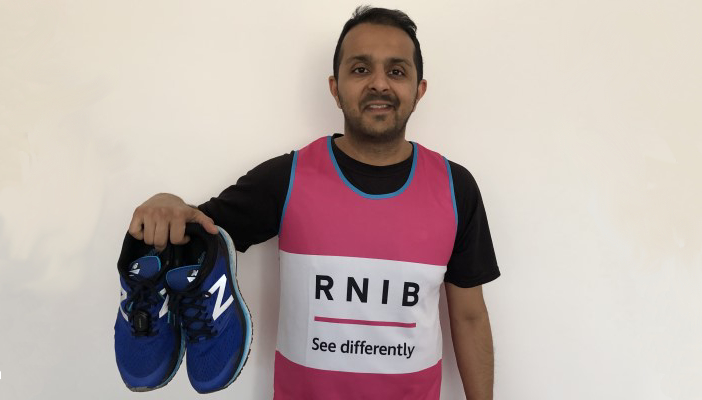Sundip Tailor with his running shoes in his Team RNIB running vest