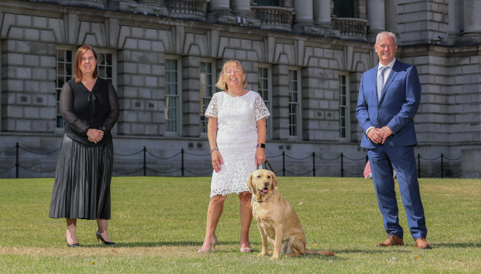 Three members of RNIB and HSCB stand on a lawn outside an old building