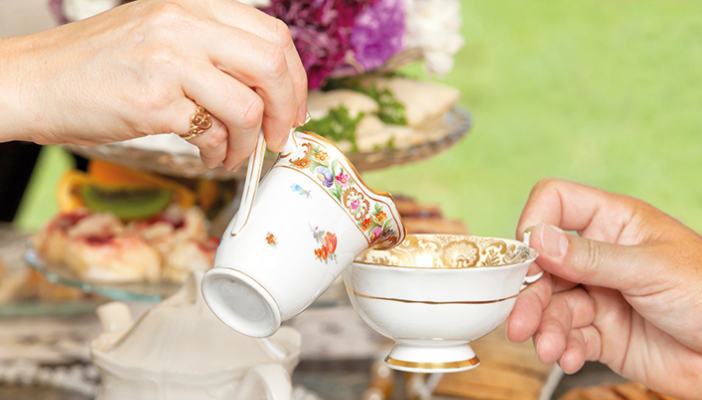 A person pours milk from a china jug into a china cup at a tea party