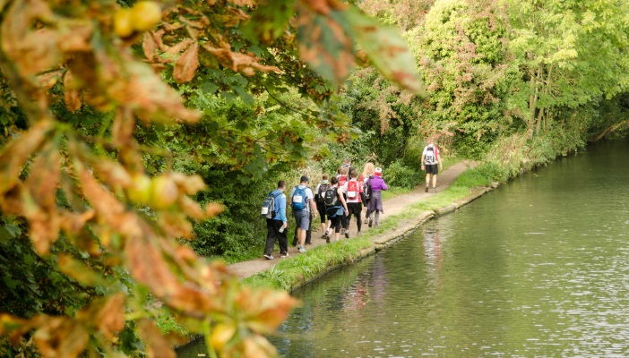 Image shows a group of people walking along the side of the river with lots of greenery around