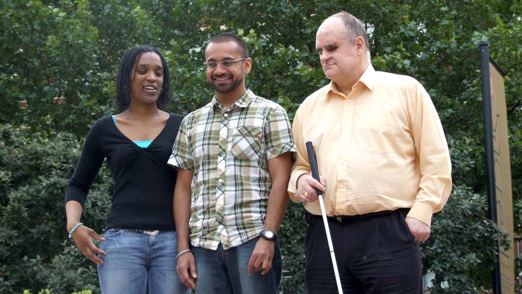 Three people with sight loss in a park