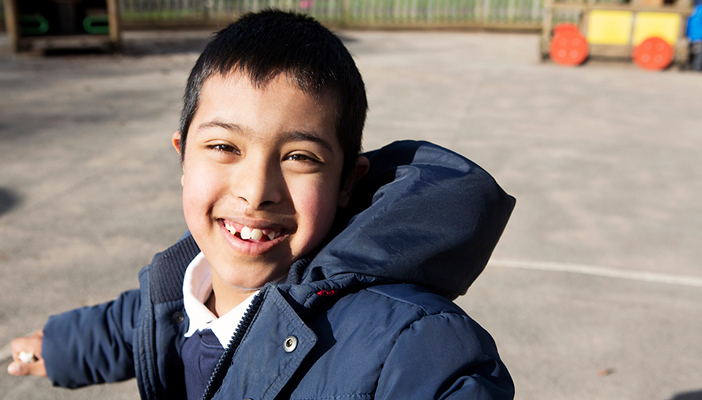Young boy pupil smiling whilst playing in the playground