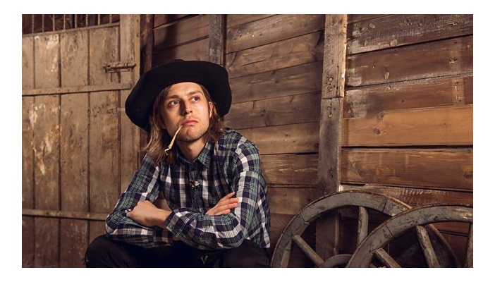 Photo shows Tom in a barn with a piece of straw in his mouth looking into the distance