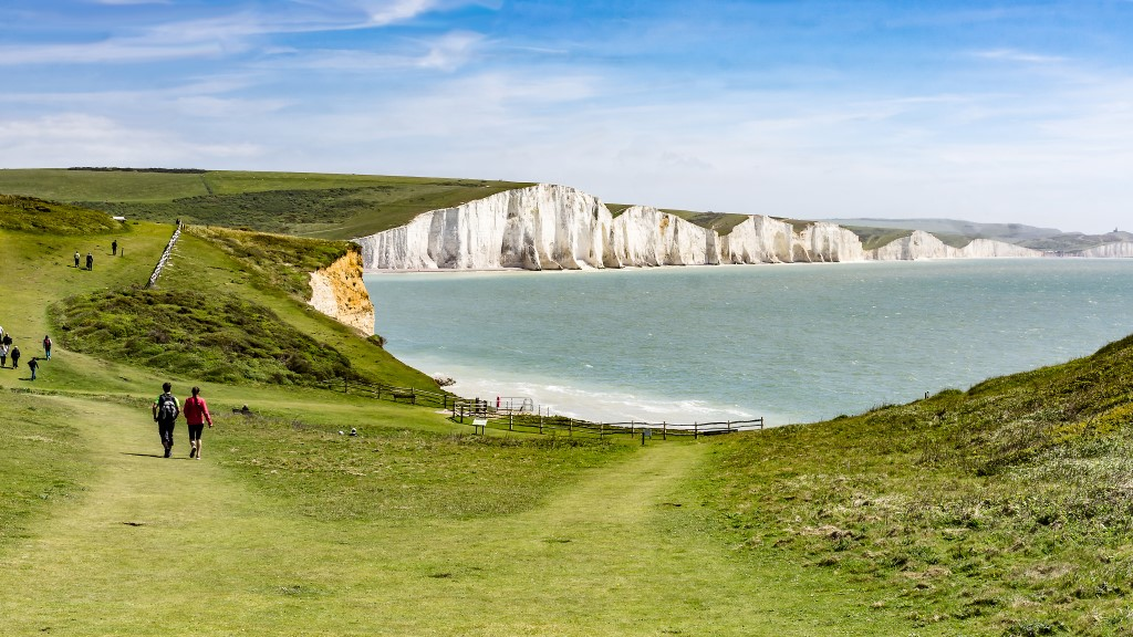 View of the sea from the South Downs with people walking along the cliffs