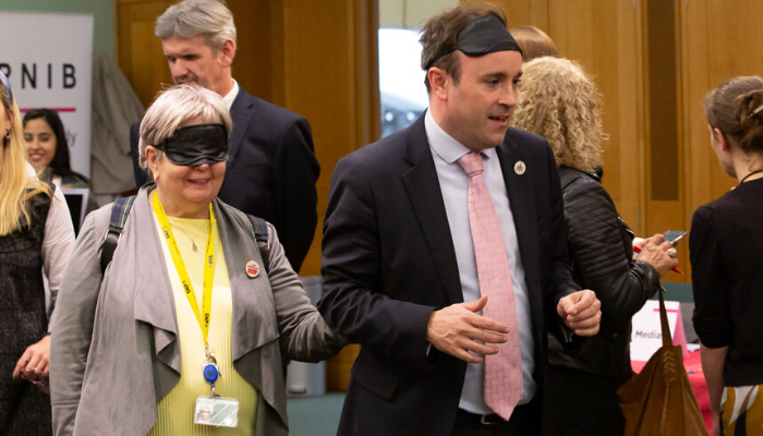 Two MPs, one wearing a blindfold and being guided by the other.