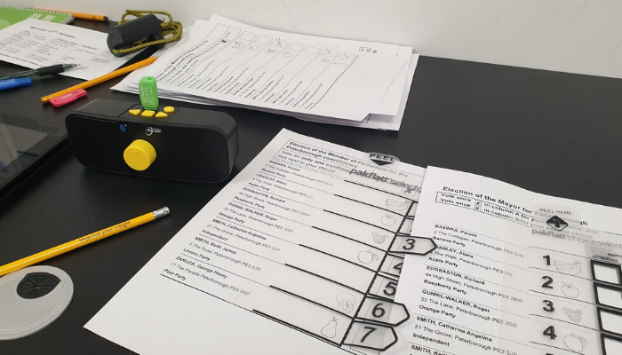 Image shows ballot papers with tactile voting devices on them set on a desk next to pencils and an audio device.