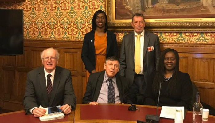Marsha De Cordova MP seated next to Lord Lowe on her left and Jim Shannon MP on his left, with Lord Blunkett and Florence Eshalomi MP standing behind them, at a table in parliament.