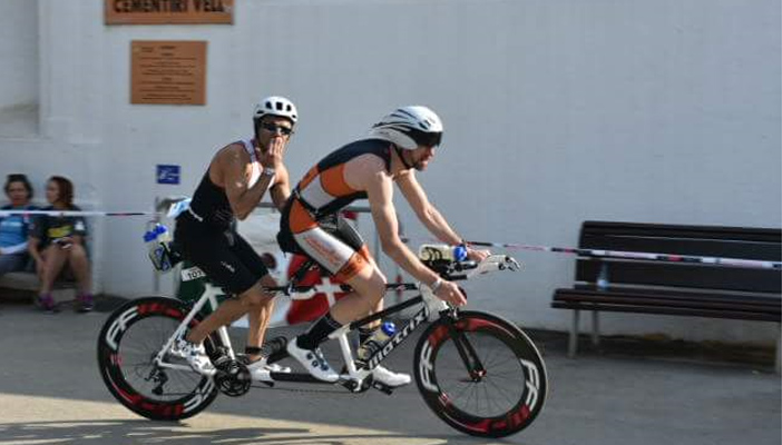 Image shows Haseeb Ahmad cycling in his kit and protective gear alongside another individual