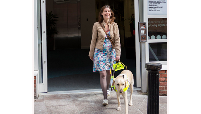 Nicki and her guide dog outside